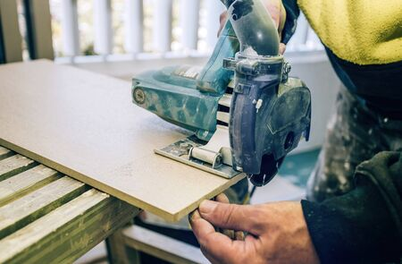 Master cuts the tile using an angle grinder with special diamond disc. Angle grinder in operation, close-up view