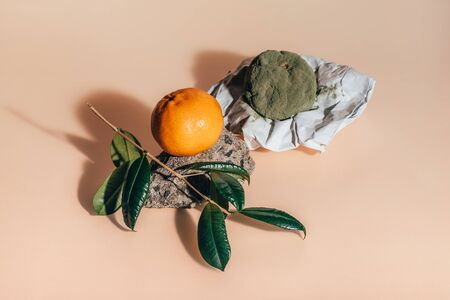 Fresh and rotten mandarins. Spoiled tangerines with green mold and fungus on paper and a ripe fresh one on a rock with a green branch with leaves on coral background.