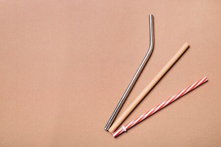 Different kinds of straws. Reusable bamboo, stainless steel and single-use plastic. Zero-waste, sustainability concept. Фото со стока