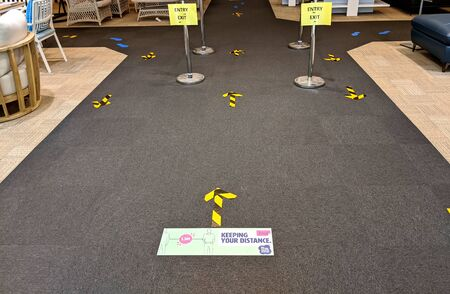 Distance stickers and signs fixed over the floor at the shop queue for the people to follow social distancing to avoid infection of coronavirus disease.
