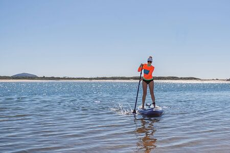 Slim woman on stand up paddle board on a quiet sea with clear blue sky. Relaxing in ocean