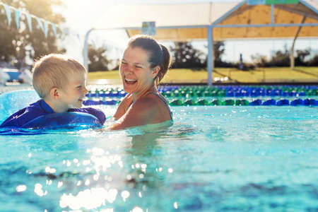 Mother and little boy in swimming pool outside in sunny day, smiling face, enjoy in the water, close up portrait. Stock fotó