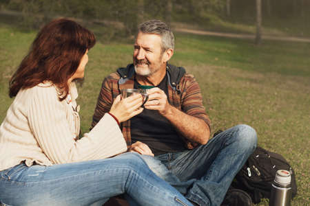Happy middle-aged couple in love sitting on a blanket in the grass in park, look at each other, smile and drink tea or coffee