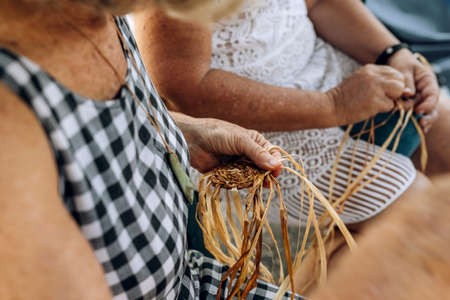 Two old females weaving baskets on the craft workshop. Hands holding the craftwork, close up shot.