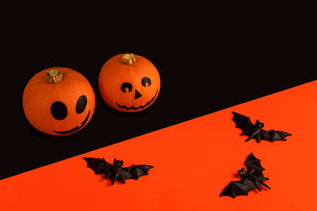 Little pumpkins with painted faces for Halloween and bats on orange and black background