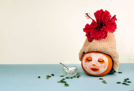 Pumpkin with painted face and facial mask, towel with flower, pumpkin sseeds and powder in glass bowl on pastel blue background. Spa concept, Helloween, Copy space.