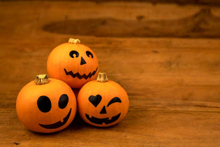 Little pumpkins with painted faces for Halloween on wooden background Stock Photo