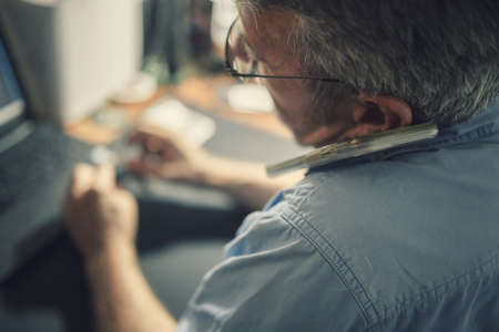 A senior man sitting at a desk in front of a laptop computer