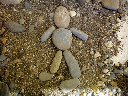 Summer vacation impressions - the children laid on the sand different figurines of stones - man