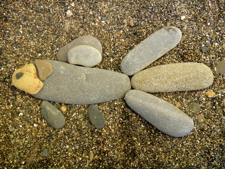 Summer vacation impressions - children put different stone figurines on the sand - a fish