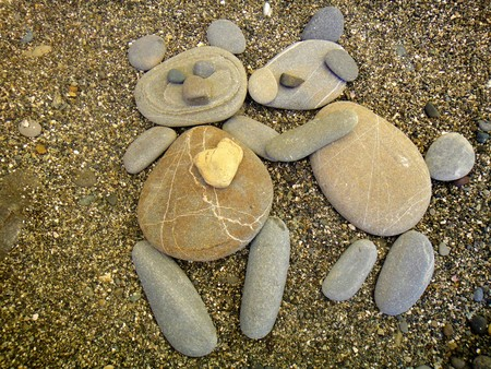 Summer vacation impressions - children laid different stone figurines on the sand - bears in love