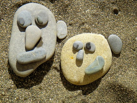Summer vacation impressions - children laid different stone figures on the sand - faces - man and woman Stock Photo