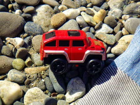 Summer vacation impressions - handmade blanket from old jeans lies on the sand, near a forgotten red toy machine Stockfoto