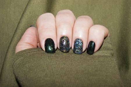 Womens hands - beautiful green manicure, nail polish on nails of different shades of green, with a slight sheen and large shimmer Stock fotó