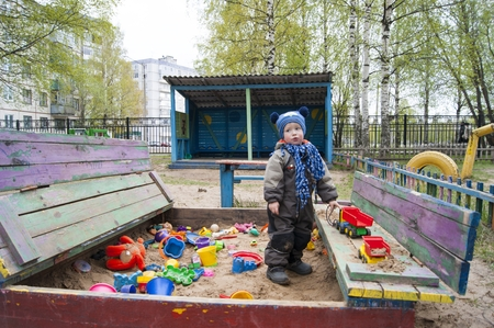 A little boy of three years old on a cool spring sunny day playing in the sandbox of a kindergarten, showing a variety of emotions about how many toys he has - spring, coolness, warm clothes