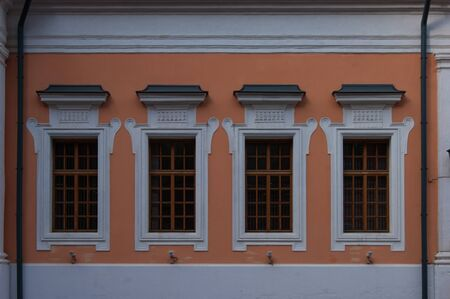 Windows in white frames with bars on the orange wall of an ancient building. Vintage. Ancient architecture. Story. Design