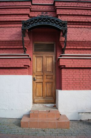 A beautiful door made of natural wood is varnished under an openwork black wrought iron porch on an old red brick building. Porch, entrance. Historic center, old architecture