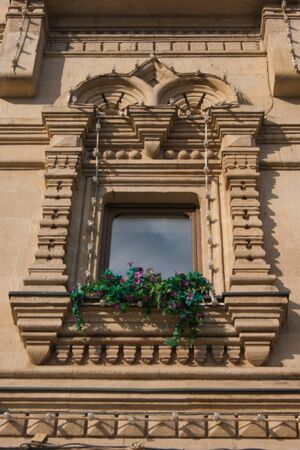Beautiful vintage window on an old building with fresh flowers on a windowsill. Architecture, life, plants, design