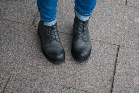 Foto di una parte del corpo umano. Le gambe femminili in stivali neri unisex e jeans stanno con i calzini all'interno. Viaggio, comfort, convenienza. Dubbi, modestia, incertezza, riflessioni. Archivio Fotografico