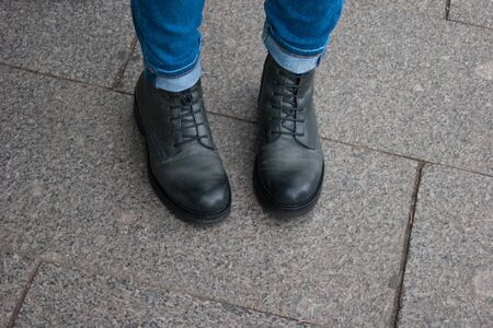 Photo of a part of the human body. Female legs in black unisex boots and jeans stand with socks inside. Travel, comfort, convenience. Doubts, modesty, uncertainty, reflections. Foto de archivo