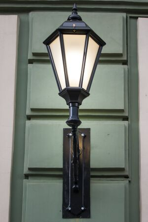 Photo of a street design. A vintage electric lamp on one of the buildings resembles an old lamp with a lamp inside. Green, beige, light, lighting