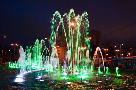 Landscaping - a beautiful fountain illuminated by luminous green lights against a dark blue night sky. Lighting, night, lights, radiance, fairytale, surreal, beauty