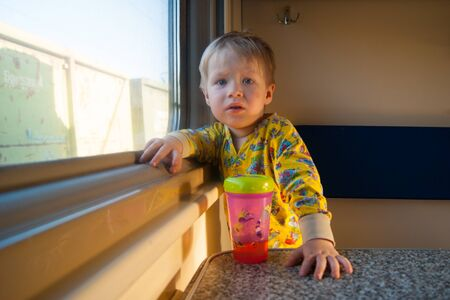 A bright cute three-year-old boy in yellow pajamas rides on a train by the window, behind which a dull landscape sweeps through. On the table in front of him is a pink drinker. The kid is full of emotions. Child, toddler, cute, cute, curiosity, cognition, interest, travel, railroad, transport