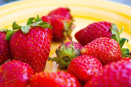 Red berries of garden strawberries with green sepals on a sunny yellow porcelain plate. Stok Fotoğraf