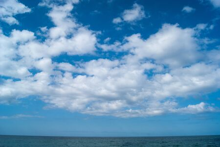 White fluffy clouds, like blond-haired horses, fly across the sky above a blue strip of the sea. Stok Fotoğraf