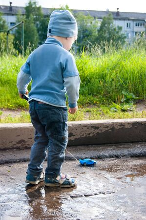 A three-year-old white boy in a blue hat, jeans and sandals plays on a cool summer day with an outdated remote control car. The kid stands with his back to the viewer on a background of green grass