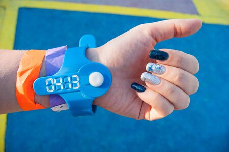 The mood color is blue - a female hand against the blue floor in colored bracelets from the water park, nails are painted in blue too