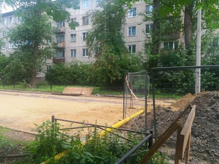 Road repair. In the courtyard of a five-story building, the road is being repaired, part of the roadbed is already covered with sand, on the right in the frame part of the sand and gravel is fenced. Russia, the city of St. Petersburg, August 2019.
