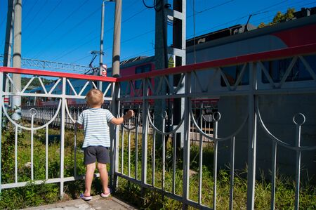 A small fair-haired boy of three years in a striped T-shirt and dark shorts stands near a fence near the railway and looks at a passing train. Summer, vacation, travel, train station Фото со стока