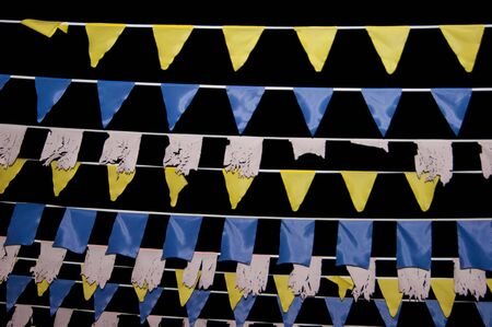 White, yellow and blue flags against the night sky hang on a tourist street