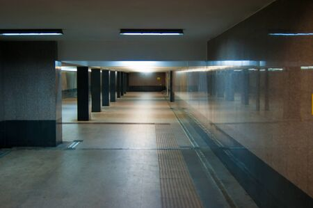 An empty underpass in marble. Columns and light create rhythm. Horizontal photo