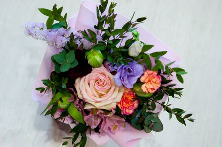 A delicate bouquet of different flowers in a light pink wrapper stands on a light background in a home setting. Horizontal photo, top view.