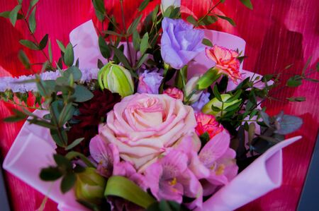 A delicate bouquet of different flowers in a light pink wrapper stands against a colorful pink wall in a home setting. Horizontal photo. Фото со стока