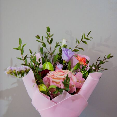 A delicate bouquet of different flowers in a light pink wrapper stands on a gray background. Square photo.