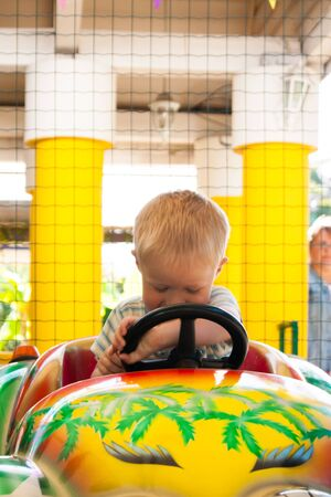 A very joyful and happy little blond boy of three years old is riding in a yellow car with a green car in the summer Riviera Amusement Park, Sochi with his back to the viewer. Rest, tropics, rest, activation, smile. Vertical photo