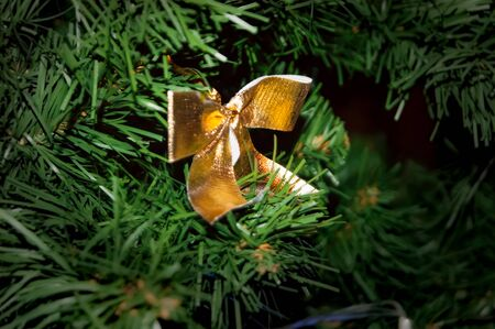 The golden bow of textile ribbon is tied to the New Year or Christmas spruce. Ideas of decorating the Christmas tree for the holiday. Interior. Mystic gifts revive miracle.