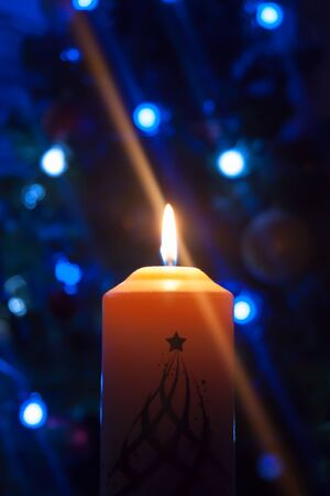 A large candle burns against the background of a garland with shining lights. Vertical photo, defocus. Mystic esoteric romance divination mood christening Christmas carol setcers Фото со стока
