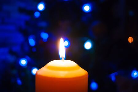 A burning orange candle on a dark background with blue lights - a Christmas New Years eve divination mystic esoteric romance love mood. Horizontal photo, side, focus or defocus.