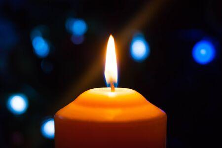 Eine brennende orangefarbene Kerze auf einem dunklen Hintergrund mit blauen Lichtern - eine mystische esoterische Romantik-Liebesstimmung der Weihnachtssilvester-Wahrsagung. Horizontales Foto, seitlich, Fokus oder Defokus.