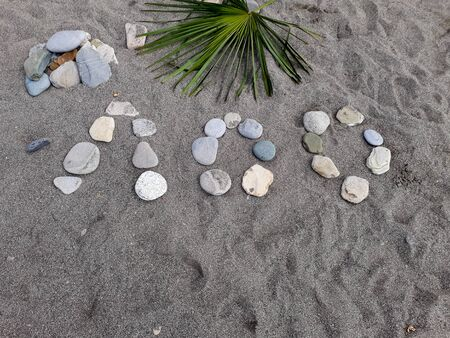 Stones on a large sand laid out the name of a resort town in Russia, translated from Russian - Loo. Beach, Black Sea coast, summer, vacation, traces on the sand.