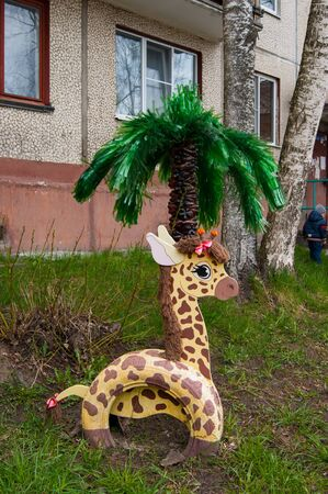 Decor garden in the courtyard of an apartment building in a provincial city - giraffe from car tires and plywood and palm tree from plastic bottles. Spring.