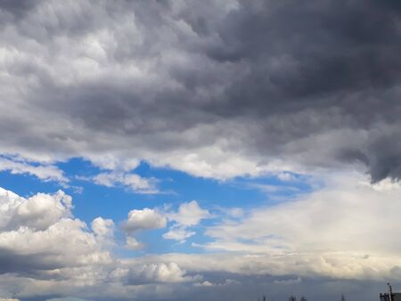 Heavy gray rain clouds in the blue sky. Atmosphere, air, cloudy, soon rain. Background for a website or blog