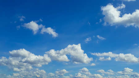 White fluffy clouds in the blue sky. Summer, cloudy. The air, the atmosphere. The background for a website or blog.