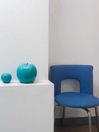 Details of the interior - a white wall, office chairs and two ceramic apples of turquoise color. Banco de Imagens