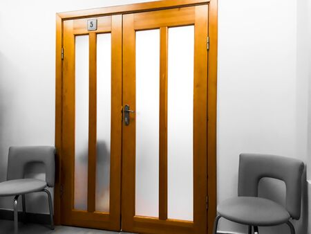 Detail of the interior, design - wide wooden doors and two office chairs next to them. Office, hall, room