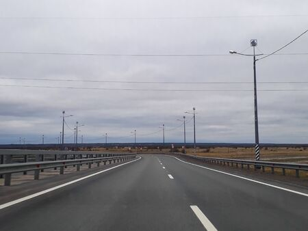 A road or a highway, the highway stretches to the horizon. View from the car window. Journey, the way home. Cold northern nature, summer, gray cloudy low sky.